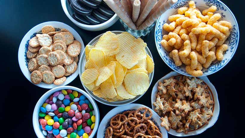 A group of bowls on a table full of processed food.
