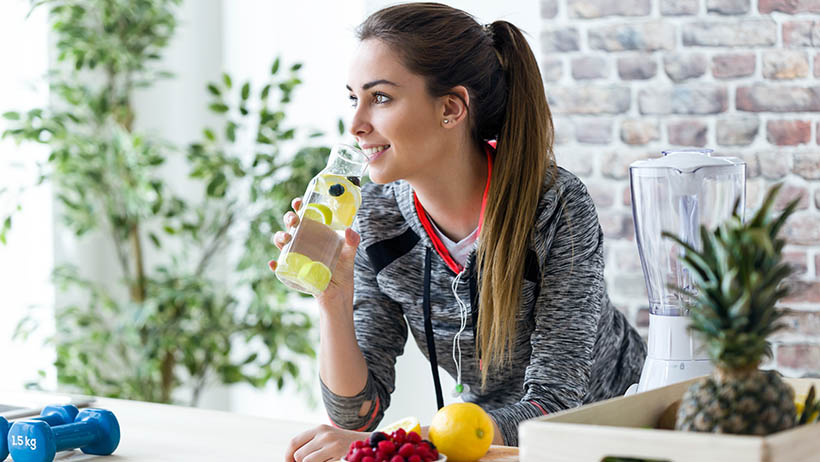 Smiling woman holding a bottle of green juice