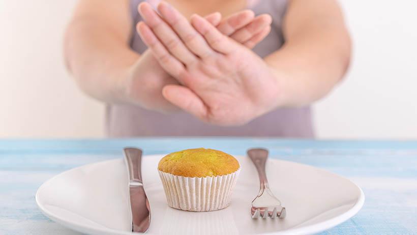 Woman refusing a muffin