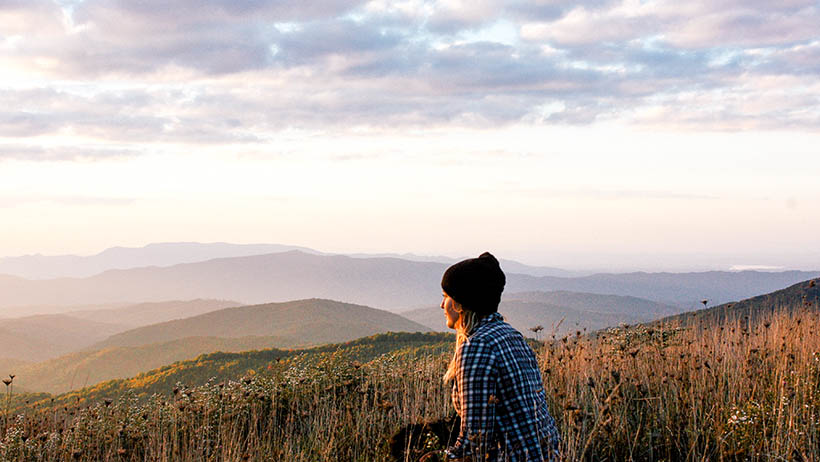 A woman sitting on a hill watching the sun set.