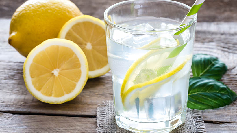 A glass of water with sliced lemon and herbs