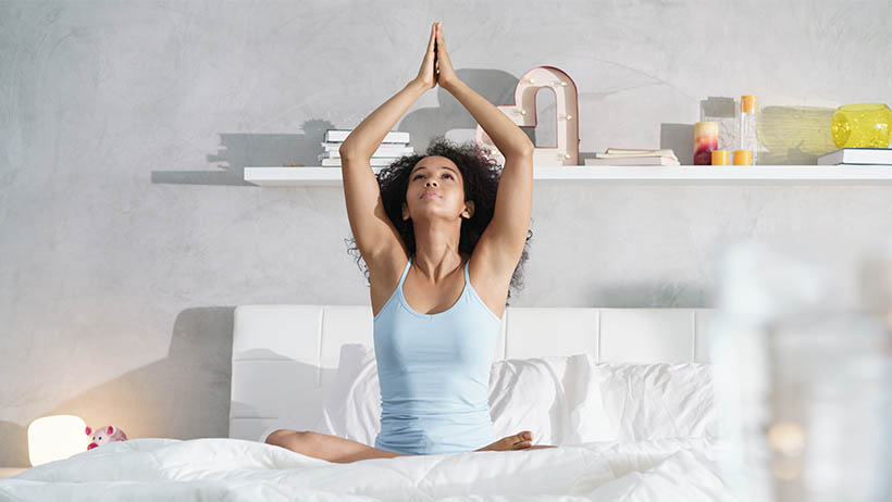 A woman sitting on her bed doing yoga.