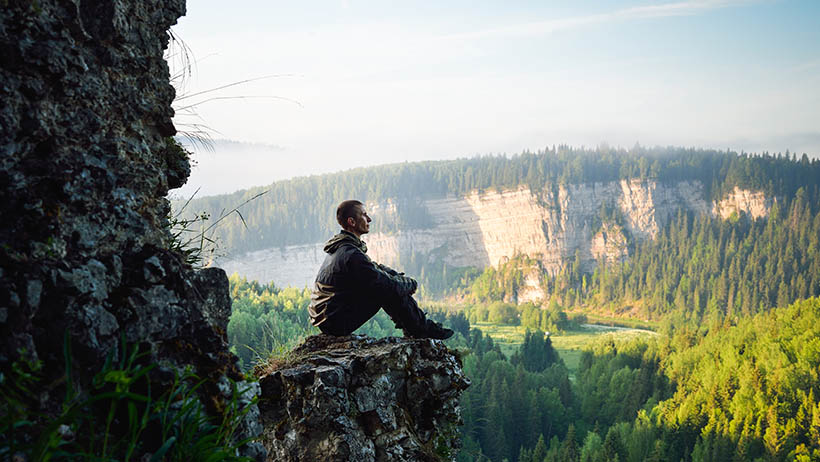 Man sitting on exposed cliff meditating