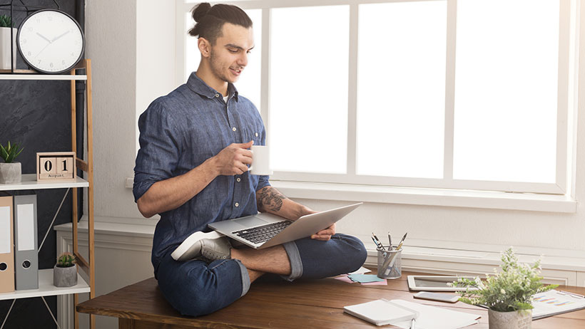 Man with good posture sitting with a laptop on his lap.