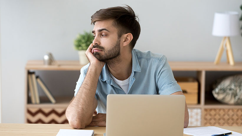 Man sitting at his work desk, looking distracted.