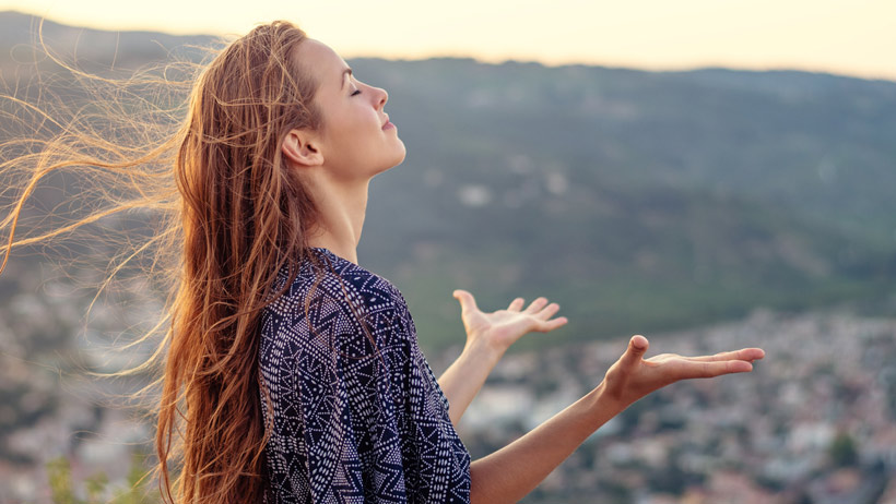 A calm woman standing outside with her arms outstretched.